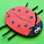 ladybug craft made out of cardboard, sticks and paint.