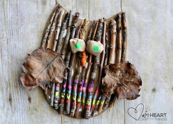 Finished stick owl craft for kids laying flat on a faux wood background