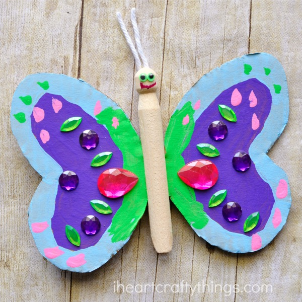 wooden peg and cardboard butterfly craft laying on a faux wood background