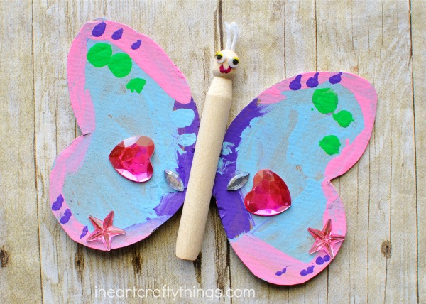 Child made wood peg doll butterfly craft.