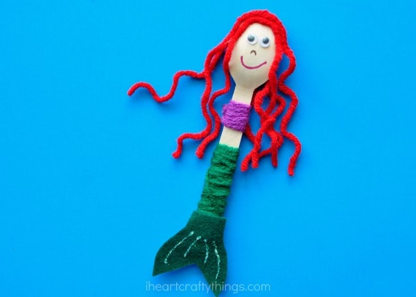 red-headed wooden spoon mermaid laying flat on a blue background