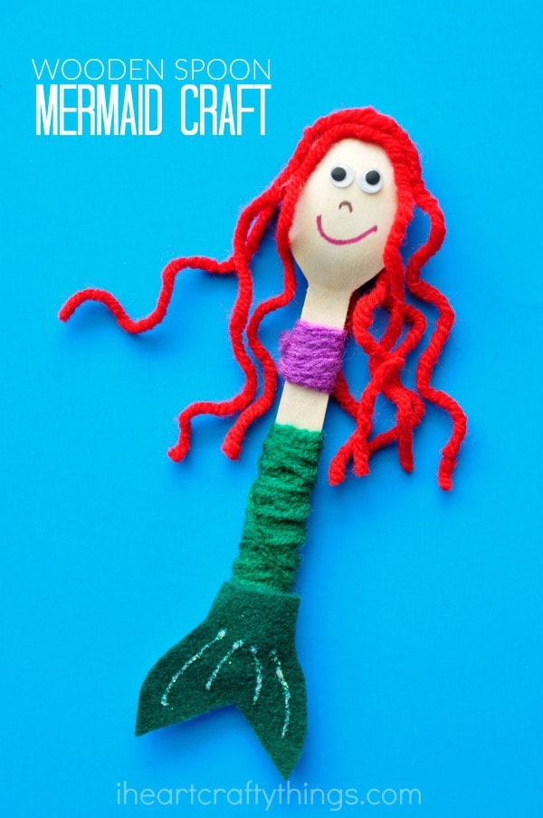 close up vertical image of red-haired wooden spoon mermaid craft laying on blue background