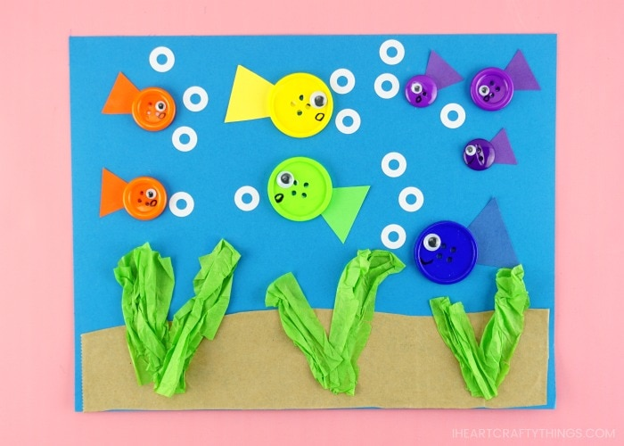 horizontal image of completed button fish craft project laying on a pink background