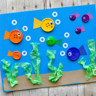 This simple button fish craft for kids is perfect as a summer kids craft and bonus, there are so many great books you can use to go along with this craft. The buttons add a perfect texture to the fish craft since they pop off the page and the little hole reinforcement labels used as bubbles are perfect for kids who love to play with stickers.