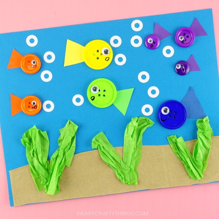 close up image of finished button fish craft on a pink background