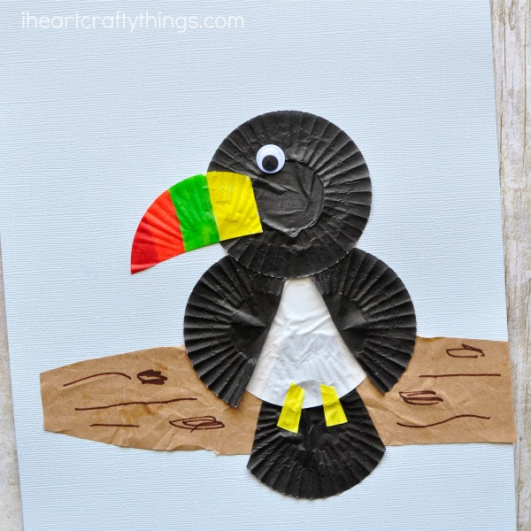 This cupcake liner toucan craft is simple to make and the brightly colored beak gives the craft such a fun pop of color. Fun bird craft for kids, cupcake liner crafts, summer kids craft and preschool crafts.