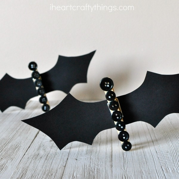 This clothespin button bat craft makes a great Halloween kids craft. It's so fun and versatile for Halloween. You can stand them up on a shelf as a cute Halloween decoration, add a magnet to the back of them and use them to hold up other artwork on your fridge or string a line of them together and make a fun bat banner for a Halloween decoration.