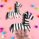 Close up image of person with their fingers inside the zebra finger puppet with another finger puppet out of focus in the background.