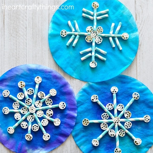 Painted coffee filters, pinwheel pasta and paper straws come together to create awesome texture in this fun kids snowflake craft. Fun winter craft for kids, preschool craft, and symmetry craft for kids.