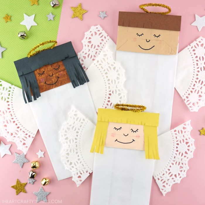 Three paper bag angel crafts laying at different angles on a pink background with star stickers and bells scattered around.