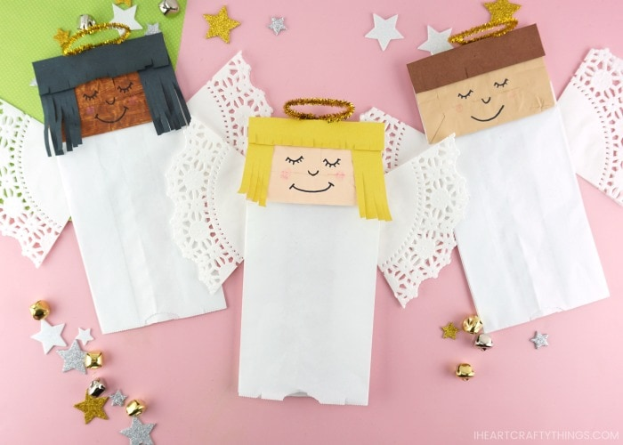 Horizontal image of three paper bag angel crafts laying next to each other on a pink background with stars and bells scattered around.
