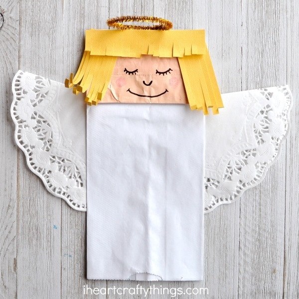 Paper bag angel craft laying on a white wood background.