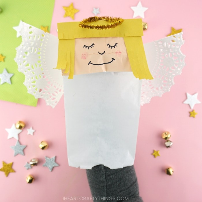 Close up image of how to place your hand and arm inside the paper bug angel to use it as a puppet.
