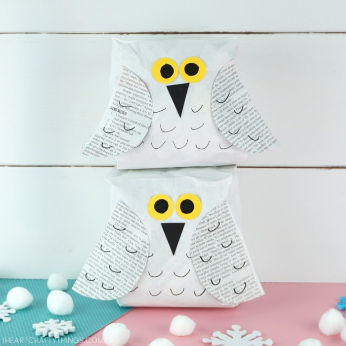 Two snowy owl crafts, one laying on top of the other in front of a white shiplap background with white pom poms scattered around the bottom.