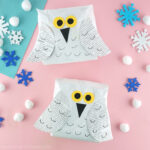 Two snowy owl crafts made from paper bags laying face up on a pink background with snowflake stickers and white pom poms scattered around.