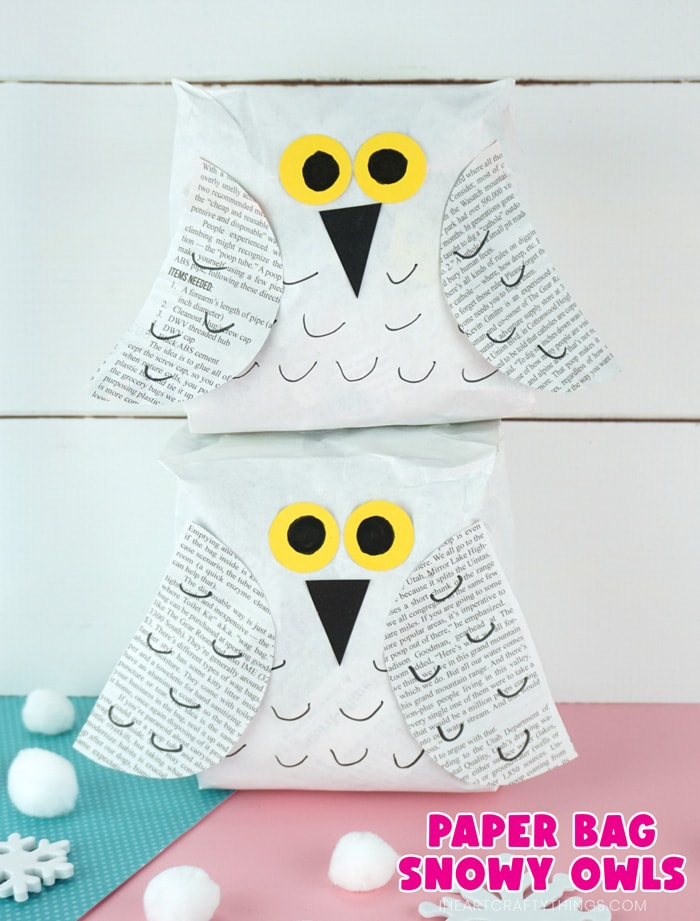"""Vertical close up image of two snowy owl crafts one laying on top of the other in front of a white shiplap background with the text """"paper bag snowy owls"""" in the bottom right corner."""