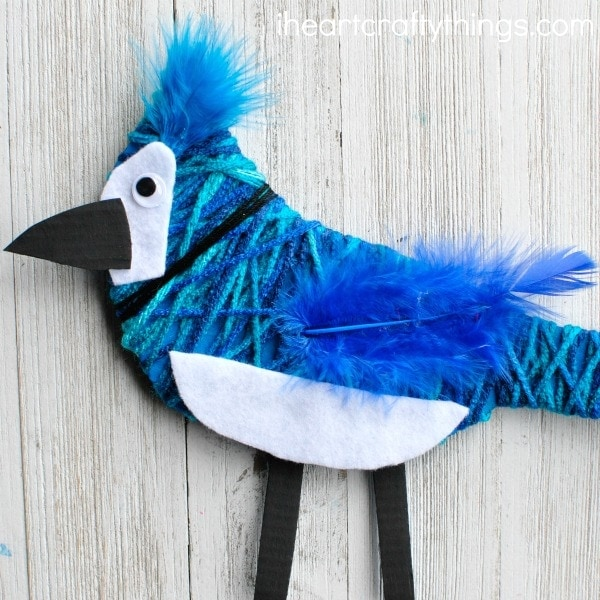This yarn wrapped blue jay craft is not only stunning but it's a great fine motor activity for kids. Fun bird craft for kids and preschool bird craft.