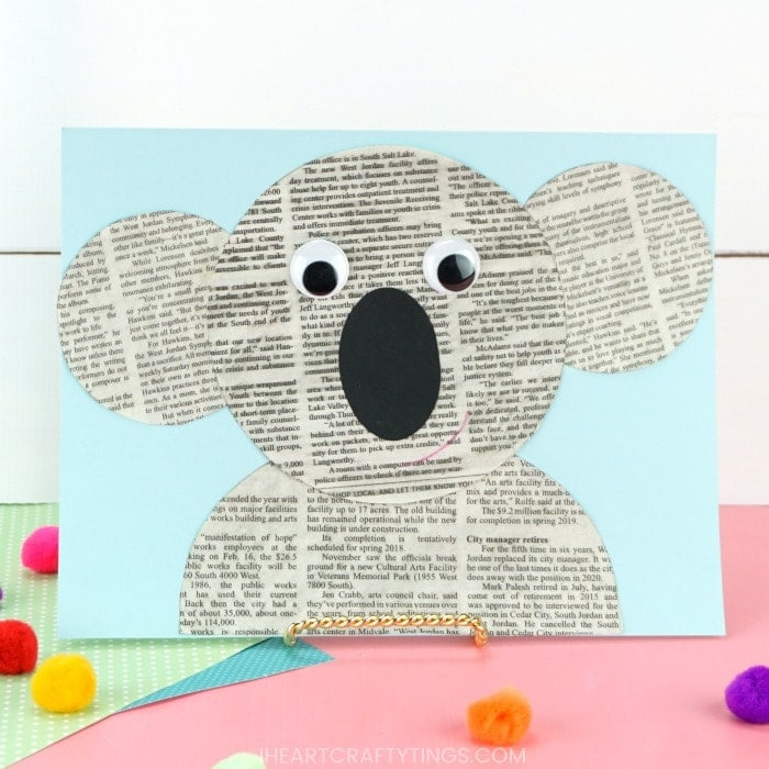 newspaper koala craft propped up on a pink table with a white shiplap background