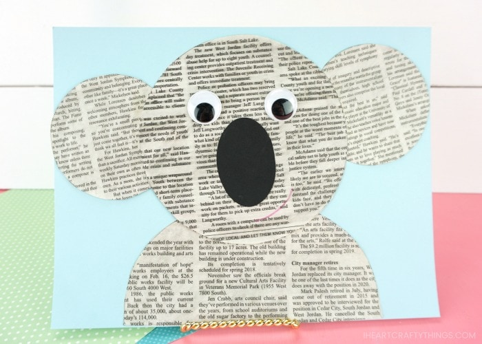 horizontal image of newspaper koala craft propped up pink table with white shiplap background
