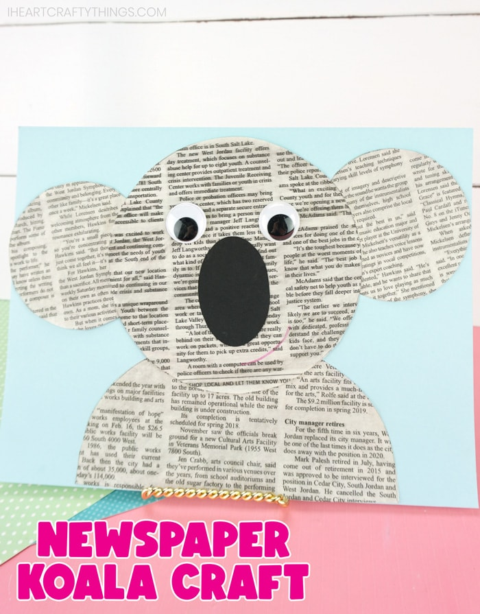 "vertical image of completed koala craft propped up on a pink table with a white shiplap background with the words ""newspaper koala craft"" at the bottom in pink text."