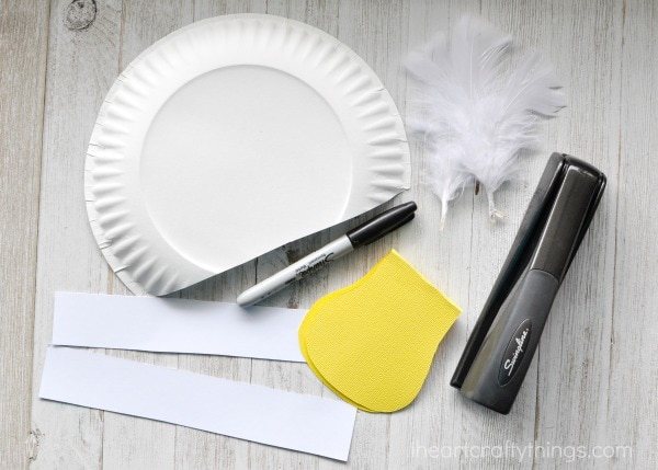 Make two creases in the middle of your folded bird beak so you have a flat surface to glue it onto your paper plate. Glue the beak onto your paper plate. & Silly Paper Plate Bird Hats Your Kids will Love | I Heart Crafty Things
