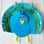 Beautiful yarn weaved paper plate peacock craft for kids. Fun bird craft for kids, peacock kids craft and summer crafts for kids.