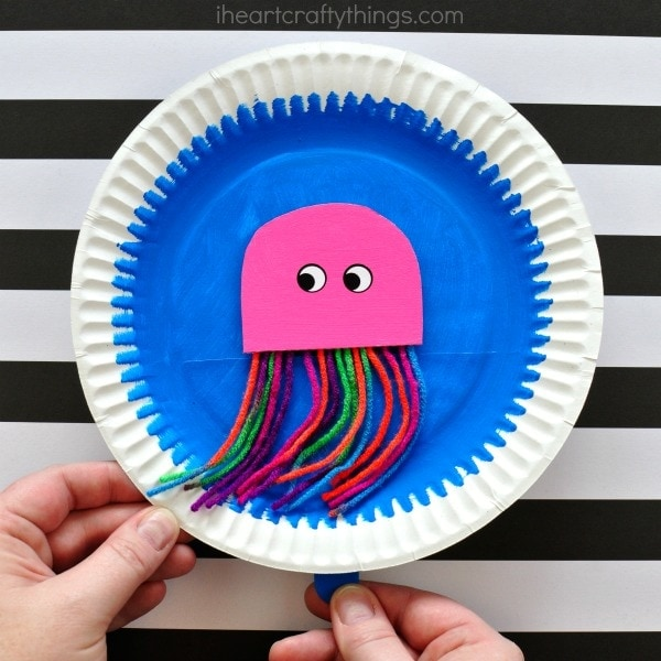 Kids move the craft stick behind the paper plate and watch as their colorful jellyfish swims around and around on the paper plate. So much fun huh?! & Paper Plate Swimming Jellyfish Craft | I Heart Crafty Things