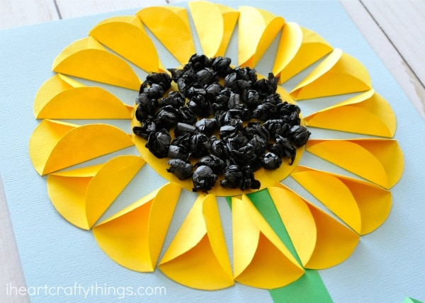 Folded paper sunflower craft i heart crafty things scrunch up a handful of black tissue paper squares into small balls add glue all over the inside yellow circle of your sunflower craft and add your black mightylinksfo Choice Image
