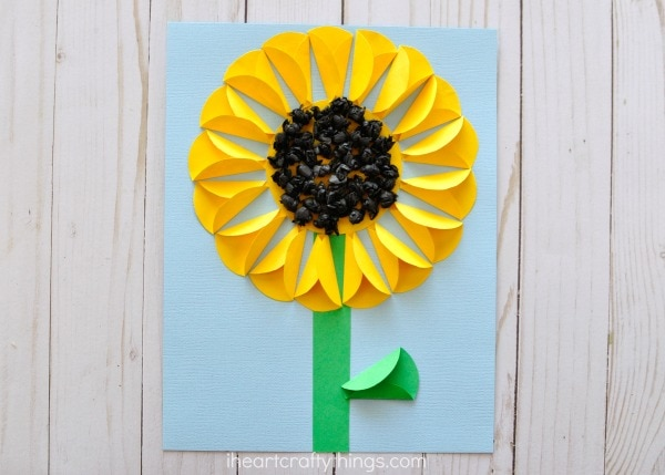 Folded paper sunflower craft i heart crafty things glue your stem and the large yellow circle onto your light blue cardstock fold two sides of your yellow paper circles inward making a smaller point on one mightylinksfo