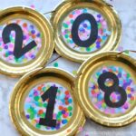 Make your New Year's Party extra festive by making this paper plate New Year's Eve Banner. It's the perfect festive compliment for a New Year's Eve party since it is made with black, gold and colorful confetti. You won't believe how easy it is to put together. Fun New Year's Eve crafts for kids.