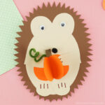 Paper hedgehog craft holding a 3D paper pumpkin laying flat on a pink background with the corner of a green polkadot piece of scrapbook paper showing in the top right corner.
