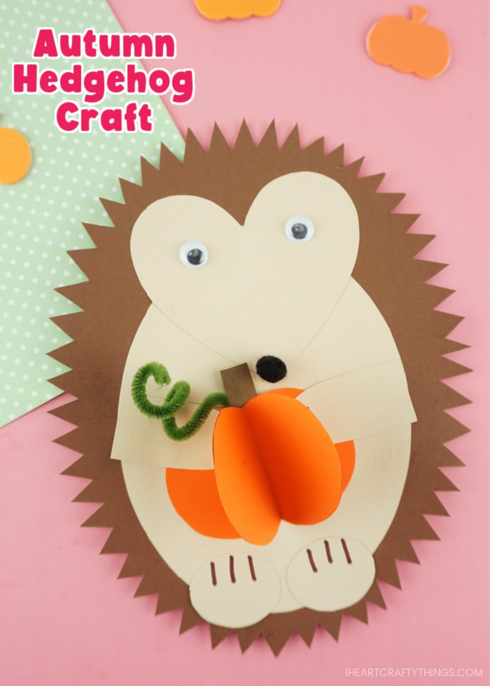 """Vertical close up image of paper hedgehog craft holding a 3D paper pumpkin with the words """"Autumn Hedgehog Craft"""" in the top left corner."""