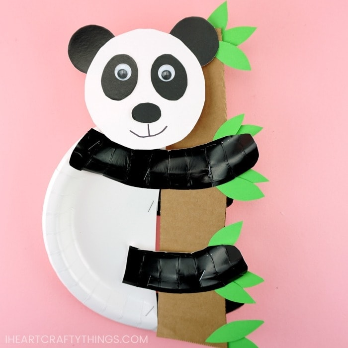 Square image of paper plate panda bear craft holding onto cardboard tree trunk with leaves.