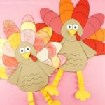 Two paper turkey crafts side by side. One made with colored paper and one made with white paper that is colored by children.