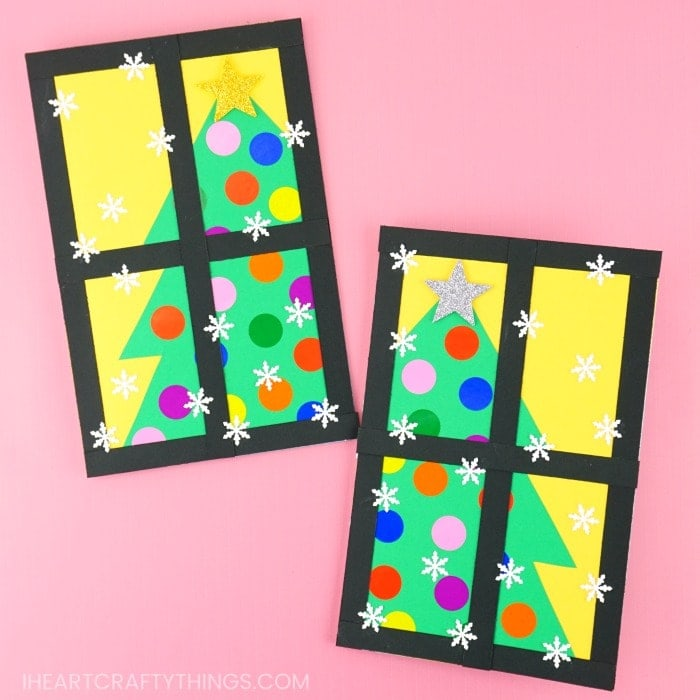 Homemade Christmas tree cards laying on a pink background