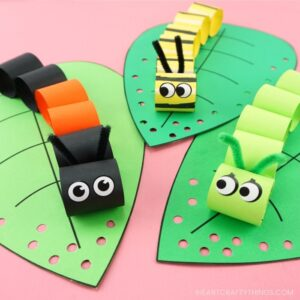 square image of three caterpillar crafts laying on a pink background