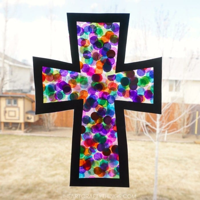 Square photo of a stained glass cross craft hanging in a window