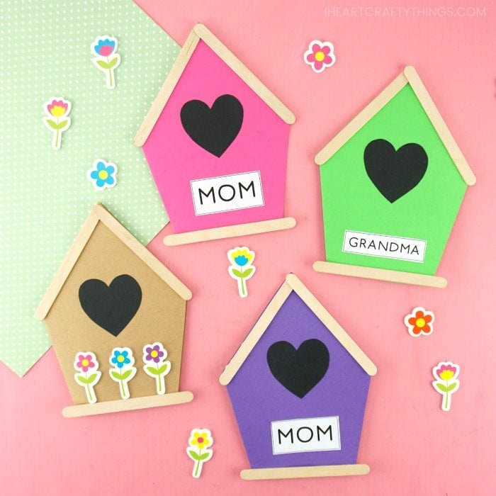 Four Mother's Day birdhouse cards in pink, green, purple and tan laying flat on a pink background with flower stickers scattered around