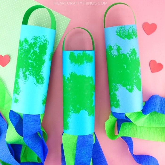 three earth day windsocks laying flat on a pink background