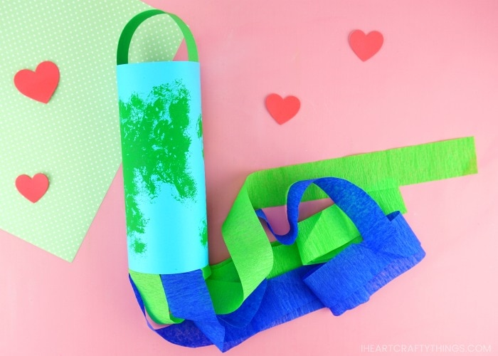 earth day windsock craft laying flat on a pink background with scattered red hearts