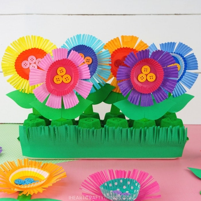 egg carton flower garden craft for kids laying on a pink table with a white shiplap background