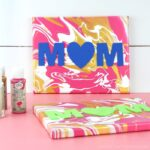 finished Mother's Day paint pouring art propped against a white shiplap background