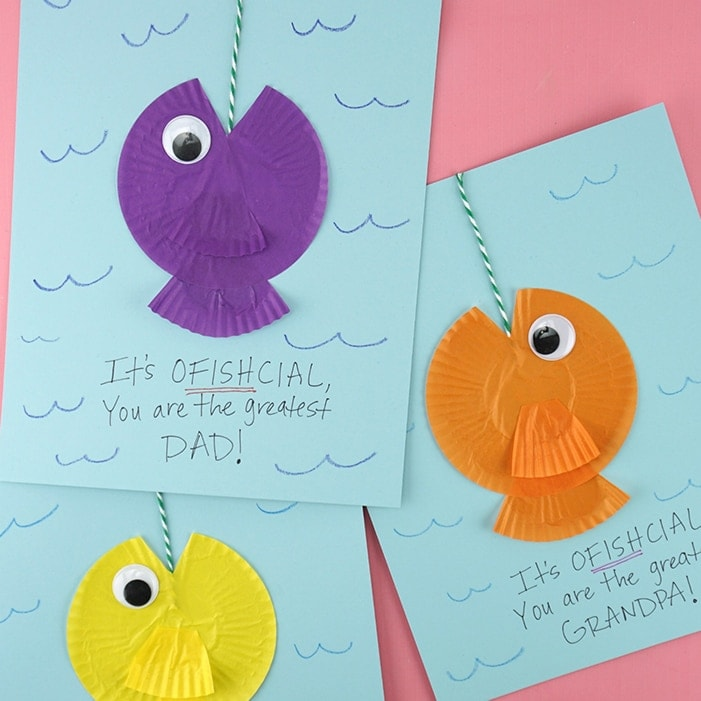 square image of three cupcake liner fish crafts for fathers day on a pink background