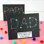 Father's Day DAD constellation craft placed on a photo stand on a pink table with colored craft poms and a blurry white shiplap background