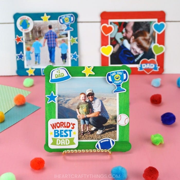 Square image of three Father's Day photo frame crafts. Front craft is in focus and back two are out of focus in front of a white shiplap background