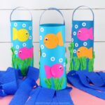 Square image of three DIY fish windsocks on a pink table with white shiplap background. Middle windsock is in focus and two back windsocks are blurry.