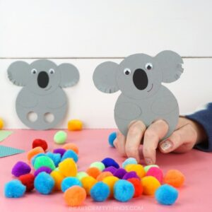square image of someone playing with a koala finger puppet with scattered pom poms on pink table and white background