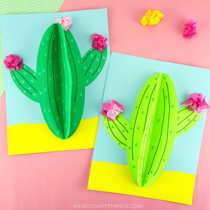 dark green and light green paper cactus craft laying flat together on a pink background