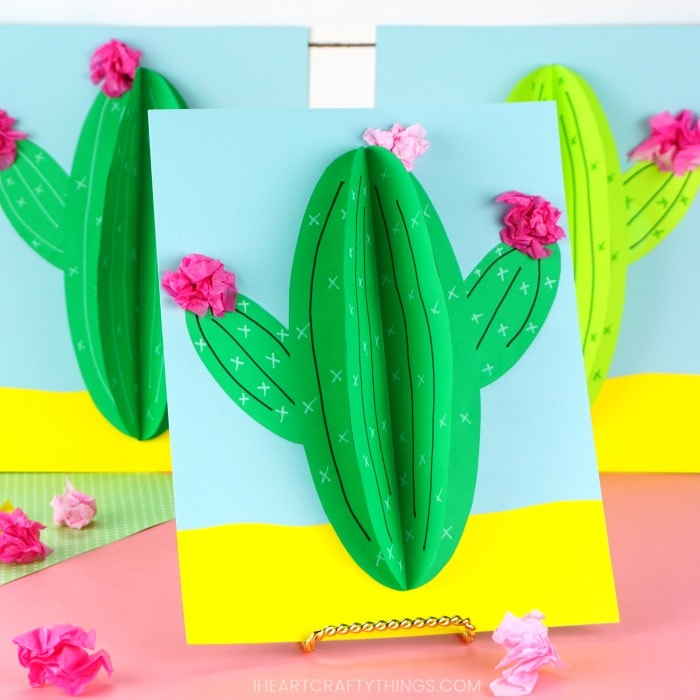 three paper cactus crafts propped up on pink table with white shiplap background