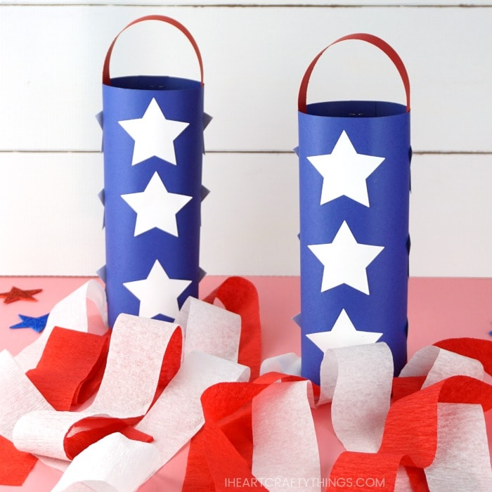 two red white and blue patriotic windsocks sitting on a pink table with a white shiplap background